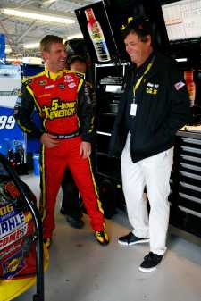 (L-R) Clint Bowyer, driver of the No. 15 5-hour Energy Toyota, talks with team owner Michael Waltrip talk in the garage - Photo Credit: Tyler Barrick/Getty Images for NASCAR