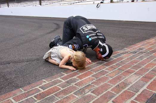 Jimmie Johnson and his daughter Genevieve Marie, kiss the Bricks at Indianapolis Motor Speedway - Photo Credit: Mike Harding