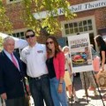 Colonial Williamsburg Foundation President and CEO Colin Campbell, Kyle Busch, driver of No.18 M&M's® Toyota Camry, and his wife Samantha in front of the Kimball Theatre in Colonial Williamsburg's Merchants Square.
