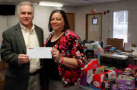Martinsville Speedway President Clay Campbell presents a check to Simone Redd of the Grace Network of Martinsville and Henry County. The track's 18th Annual Toy Drive raised more than $13,000 to provide toys for kids on Christmas Morning.)